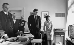 kennedy in room surrounded by people